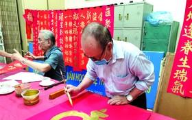 人民藝人張路書畫家與各書法家 為慈善揮春活動作好準備。
