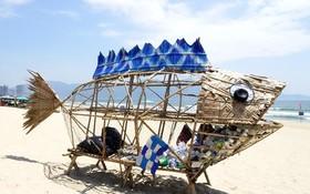 峴港市美溪海灘上用竹、椰子葉和回收材料製成的魚模型垃圾桶。