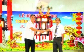"""王永勝理事長(右)向安強木器公司經理 黎德義移交""""一帆風順""""聖燈。"""