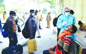 乘客在印度德里一處巴士終點站接受新冠病毒檢測取樣。