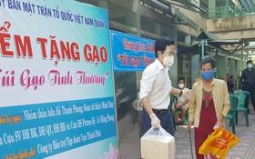第六郡越南祖國陣線委員會主席阮國洋向貧困者贈送大米。