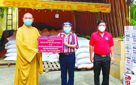 范氏明月副主席接受郡佛教會會長 釋慧功法師轉交的物資。