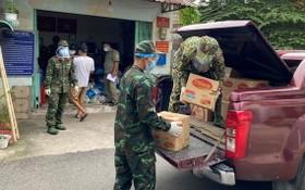 部隊力量把準備供應給民眾的食品、蔬菜裝上車。