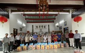 義安會館理事向貧困鄉親贈送禮物。
