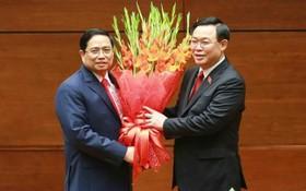 國會主席王廷惠(右)向政府總理范明政祝賀並贈送鮮花。