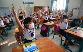 一年級小學生在課堂上高興地與老師互動。