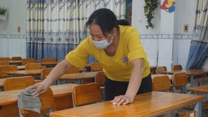 An employee is disinfecting tables before students return to schools (Photo: SGGP)