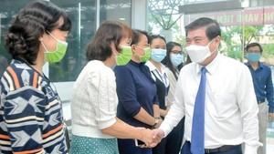Chairman of the Ho Chi Minh City People's Committee Nguyen Thanh Phong congratulates health workers of the city Center for Disease Control (Photo: SGGP)