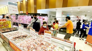 Consumers buy pork at a supermarket. (Photo: SGGP)