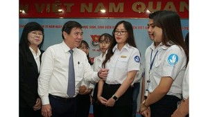 Chairman of the People's Committee of HCMC, Nguyen Thanh Phong (2nd, L) talks to schoolgirls at a meeting between the city's leaders and outstanding students in 2019. (Photo: SGGP)