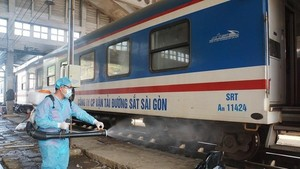 A health worker is cleaning and disinfecting a train.