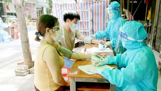 Đội tiêm vaccine lưu động tại đường Nguyễn Hữu Cầu, phường Tân Định (quận 1) đo huyết áp người dân trước khi tiêm