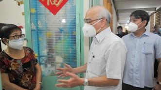 """Trưởng Ban Tuyên giáo Thành ủy TPHCM thăm hỏi các hộ khó khăn ở khu vực """"vùng xanh"""" tại chung cư 21-41 Tản Đà. Ảnh: CAO THĂNG"""