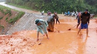 Bộ đội Biên phòng tỉnh Quảng Trị cùng người dân dọn bùn đất trên tuyến đường liên xã ở huyện Đakrông (Quảng Trị). Ảnh: NGUYỄN HOÀNG