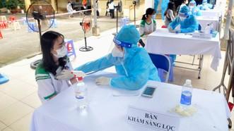 Khám sàn lọc trước khi tiêm vaccine cho các em học sinh. Ảnh: CAO THĂNG