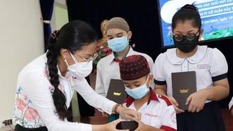 Phó Chủ tịch Ủy ban MTTQ Việt Nam TPHCM Phan Kiều Thanh Hương trao máy tính bảng cho học sinh dân tộc thiểu số