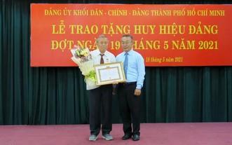 武玉國順同志(右)向阮煌同志(左)頒授55年黨齡紀念章及獎狀。(圖源:秋紅)