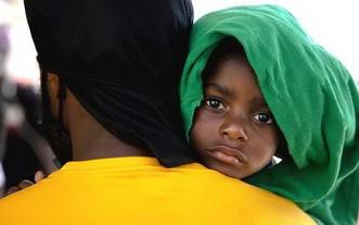 9月25日,在墨西哥阿庫尼亞城的移民收容所,一名來自海地的移民男孩和他的父親排隊向墨西哥移民官員遞交信息。(圖源:新華社)