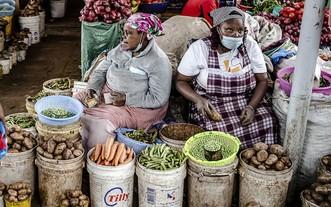女攤販在肯尼亞一家市場賣蔬菜。(圖源:聯合國)