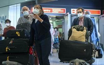 抵達倫敦希思羅機場的乘客佩戴著防護口罩。(圖源:互聯網)