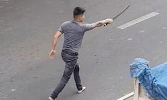 """一名男子手持長劍在馬路上氣洶洶尋找對方""""算賬""""。(圖源:視頻截圖)"""