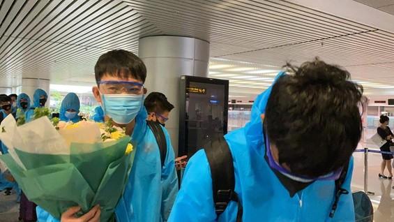 Xuân Trường cùng các đồng đội nhận hoa chúc mừng khi vừa xuống sân bay. Ảnh: QUANG TRUNG