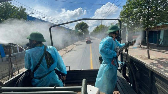 Soldiers in protective gear using high-pressure sprays sanitize streets in Binh Tan District on July 18. (Photo: SGGP)