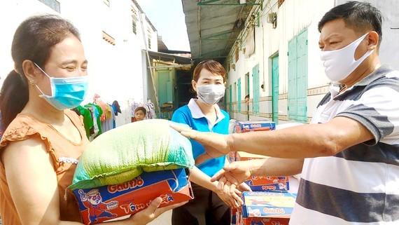 Anh Lương Ngọc Nhẹ, chủ nhà trọ ở ấp 5, xã Thạnh Phú, huyện Vĩnh Cửu, tỉnh Đồng Nai trao quà hỗ trợ công nhân ở trọ. Ảnh: TIẾN MINH