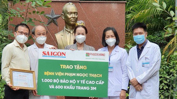 Ban Giám đốc BV Phạm Ngọc Thạch nhận bảng tượng trưng hỗ trợ từ đại diện Báo SGGP và Công ty Phúc Khang