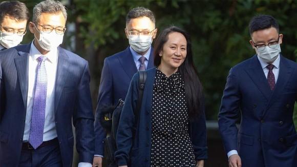à Mạnh Vãn Chu (giữa) rời nhà riêng để tới dự một phiên xử trực tuyến ở Vancouver, Canada ngày 24-9. Ảnh: Reuters