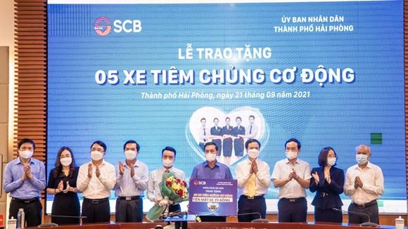 Đại diện SCB trao bảng tượng trưng tặng 05 chiếc xe tiêm chủng cơ động