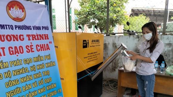 Người dân nhận gạo hỗ trợ từ chương trình ATM gạo ở phường Vĩnh Phú, TP Thuận An