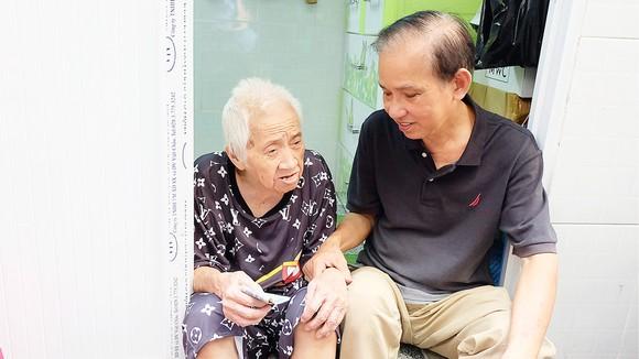 Ông Trần Văn Thanh thăm hỏi bà Trần Thị Bạch Yến, người mới được ông giúp sửa chữa nhà