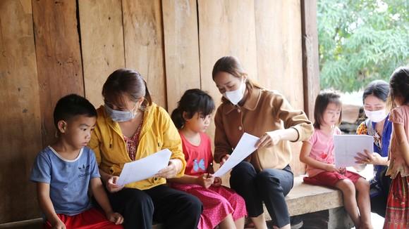 Giáo viên Trường Tiểu học Mạc Thị Bưởi (xã Ea Kiết, huyện Cư M'gar, tỉnh Đắk Lắk) đến từng nhà học sinh trong rừng sâu hướng dẫn, giao bài cho các em. Ảnh: ĐÔNG NGUYÊN