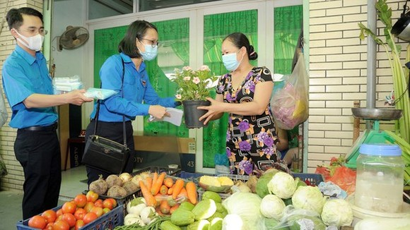Members of the Ho Chi Minh Communist Youth Union of HCMC offer plants and masks to shop owners at markets. (Photo: SGGP)