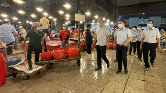 Vice Chairman of the HCMC People's Committee Duong Anh Duc leads a delegation to conduct an inspection of the epidemic prevention and control at Binh Dien whosale market. (Photo: SGGP)
