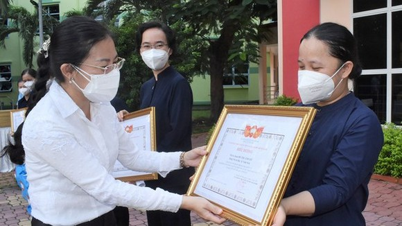 Vice Chairwoman of the HCMC Chapter of the Vietnam Fatherland Front Phan Kieu Thanh Huong presents certificates of merit to religious volunteers. (Photo: SGGP)
