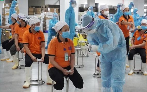 醫護人員正給北江省工業區工人採樣。(圖源:何明)