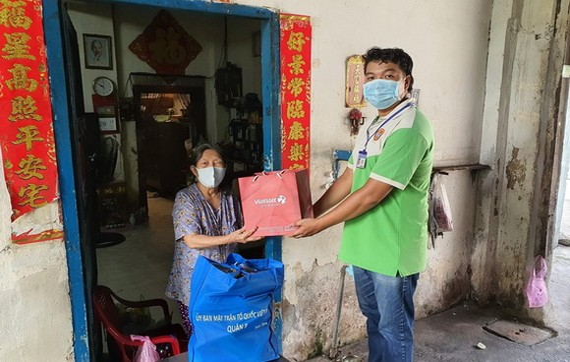 第八郡越南祖國陣線委員會代表贈送禮物給對革命有功華人家庭。