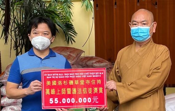 麒麟(左)代表旅美僑胞向釋慧功法師(右)捐贈善款。