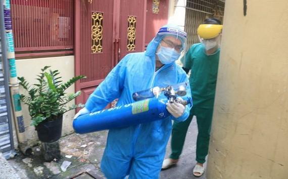國防部軍醫學院阮維新醫生抱著氧氣瓶,與第六郡第一坊醫療站人員配合急救呼吸困難確診者。