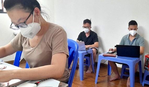 黎文孟(右)在8號新冠醫院負責輸入資訊的工作。