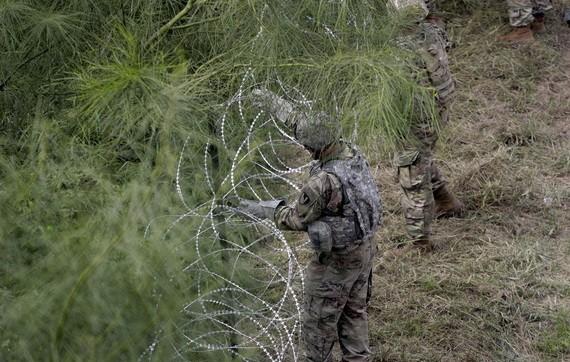 美國士兵在美墨邊境安裝鐵絲網嚴防移民入境。(圖:互聯網)