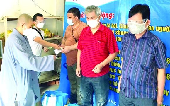 妙法寺住持釋宏心法師向視障者贈送救濟品。