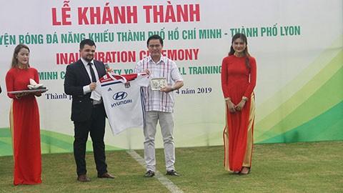 Chủ tịch HFF Trần Anh Tú nhận quà lưu niệm từ đại diện CLB Lyon (Pháp). Ảnh: Anh Trần