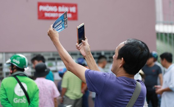 Người hâm mộ kiểm tra xem vé mua liệu có bị làm giả. Ảnh: DŨNG PHƯƠNG