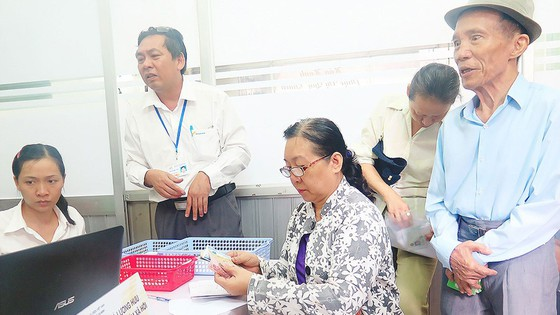 Khoảng 210.000 người có công, hưu trí, bảo trợ ở TPHCM được lãnh tiền chế độ tại nhà ảnh 2