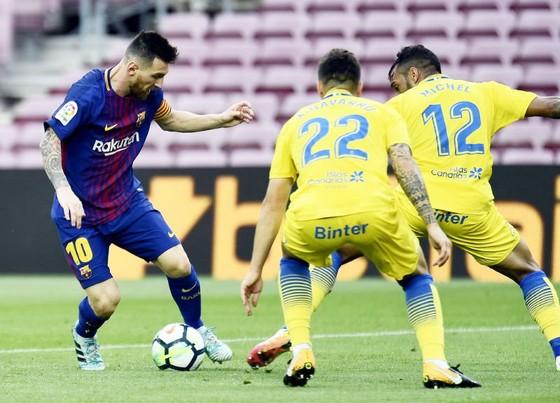 Messi (đỏ xanh) gieo nỗi kinh hoàng lên hàng thủ Las Palmas. Ảnh: Getty Images