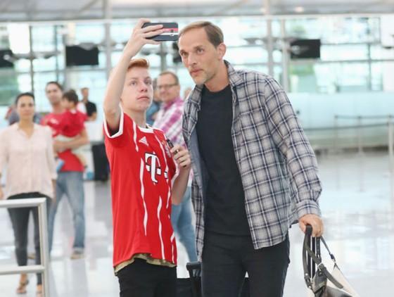 HLV Thomas Tuchel (phải) chụp ảnh cùng một CĐV của Bayern Munich. Ảnh: Getty Images