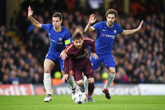 Cesc Fabregas (phải) cùng đồng đội trong nỗi lực ngăn cản Lionel Messi ở lượt đi. Ảnh: Getty Images